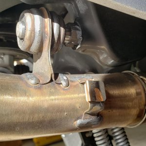Exhaust support bracket and heat shield tab on stock connecting pipes.
